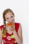 Woman biting into a slice of bread with jam
