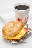 Scrambled egg and ham in sesame bagel, cup of coffee