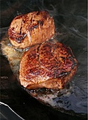 Fillet steaks sizzling in frying pan