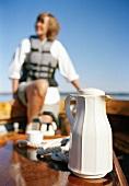 Thermoskanne auf einem Boot, Frau im Hintergrund