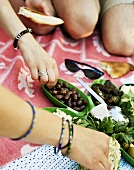 Hands reaching for olives and dip at picnic