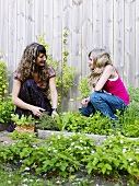 Mother and daughter in herb garden