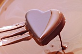 Heart-shaped chocolate on fork, dipped in chocolate sauce