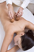 Young woman being massaged with wooden massagers