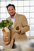Man with bag of shopping and bottle of white wine