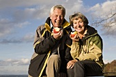 Senior couple eating apples out of doors