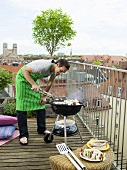 Man preparing barbecue on balcony