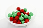 Red and green gumballs in plastic dish