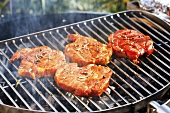 Marinated pork neck steaks on barbecue