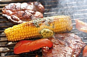 Corn on the cob with herb butter, pork steaks & pepper on barbecue