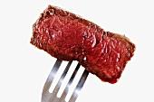 Piece of fried fillet steak on fork