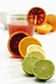 Verschiedene Zitrusfrüchte (halbiert) und Blutorangensaft