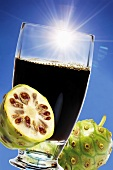 Glass of noni juice, fresh fruits
