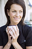 Smiling woman holding a cup in her hands