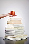 Hand holding an apple over a pile of books