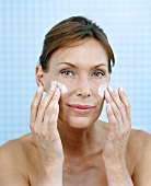 Woman creaming her face