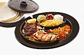 Chicken and beef fajita with accompaniments and tortillas