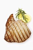 Grilled tuna steak, lemon slices and rosemary (overhead)