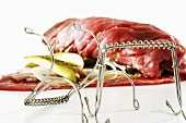 Raw beef roulade with metal clamp
