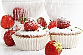 Sprinkling strawberry muffins with icing sugar