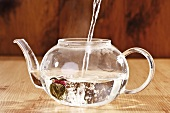 Pouring hot water into teapot (with tea flower)