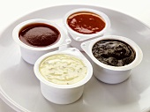 Four different dips in plastic pots