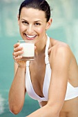 Frau im Bikini trinkt Milch
