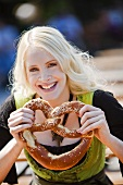 Germany, Bavaria, Munich, English Garden, Young woman holding soft pretzel, close-up