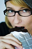 Young woman eating chocolate bar