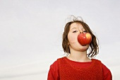 Girl (7-9) with apple in mouth