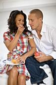Woman feeding man fruit