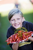 Girl holding a platter of cooked crayfish