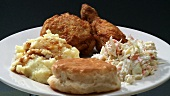 Deep-fried chicken pieces with coleslaw and potato salad