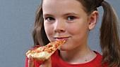 Mädchen isst ein Stück Pizza