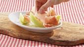 Melone mit Parmaschinken anrichten