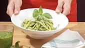 Spaghetti mit Pesto servieren