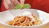 Spaghetti mit Tomatensauce in Pastateller geben