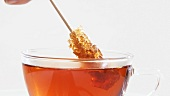 Stirring a cup of tea with a sugar swizzle stick