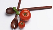 Salad servers with two tomatoes and basil leaves