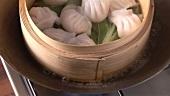 Bambuskörbchen mit Dim Sum im Wok