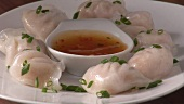 Dim sum with snipped chives and chilli sauce