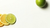 Slices of citrus fruit and a rolling lime