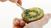 Spooning out a kiwi fruit half