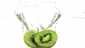 Slices of kiwi fruit falling into water