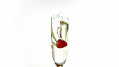 A strawberry falling into a glass of sparkling wine