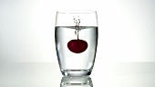 A cherry falling into a glass of water