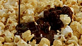 Pouring chocolate sauce over popcorn