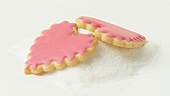 Heart-shaped biscuits with pink icing on a heap of sugar