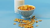 A bowl of cornflakes and a bottle of milk