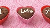 Herzförmige Schokomuffins mit Zuckerschrift